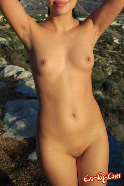 Обнаженная брюнетка с маленькой грудью в горах