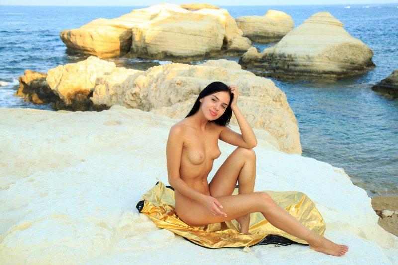 Брюнетка с волосиками на письке позирует голая у моря