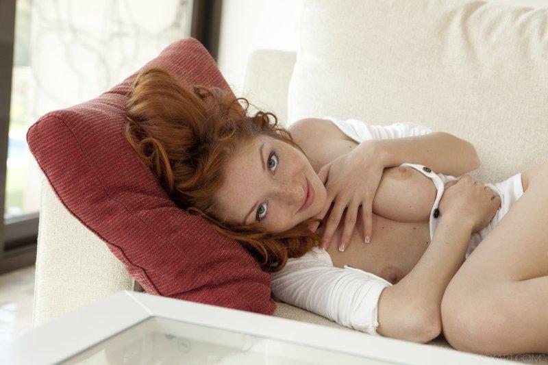 Рыжеволосая красотка скинула трусики лежа на диване